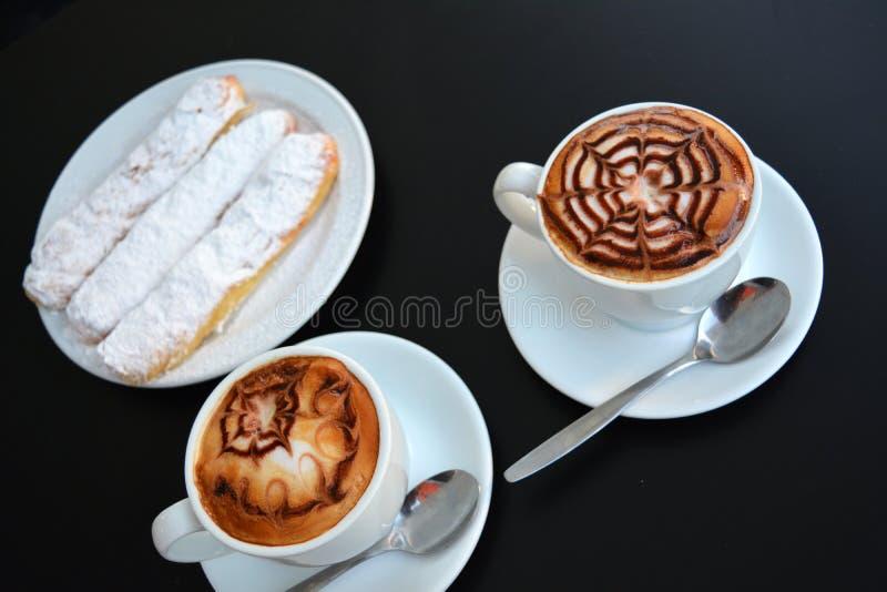 Copo do cappuccino e da sobremesa espumosos deliciosos em uma tabela preta fotos de stock royalty free