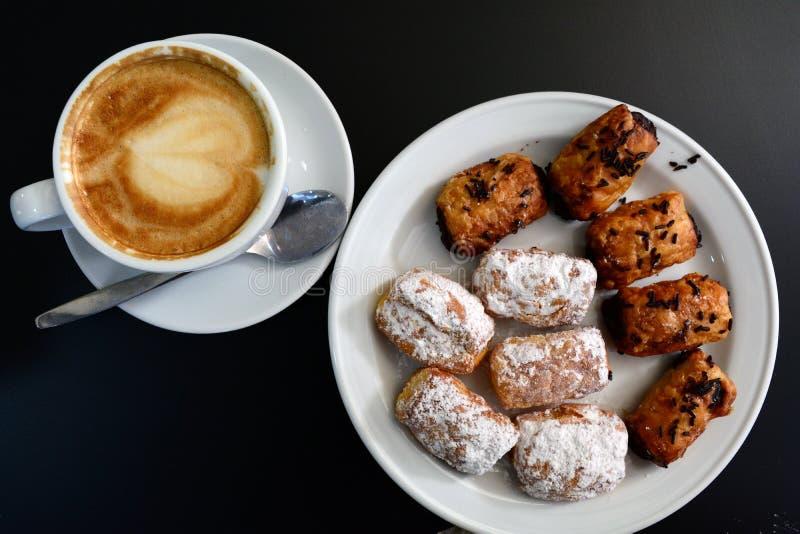 Copo do cappuccino e da sobremesa espumosos deliciosos em uma tabela preta imagens de stock