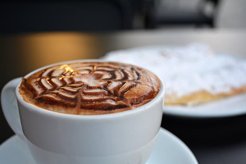 Copo do cappuccino e da sobremesa espumosos deliciosos em uma tabela preta fotografia de stock