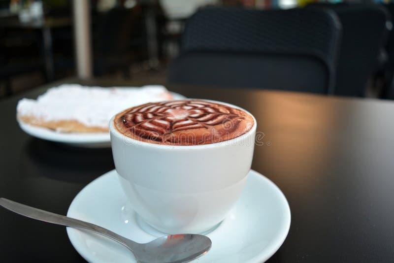 Copo do cappuccino e da sobremesa espumosos em uma tabela preta imagem de stock royalty free