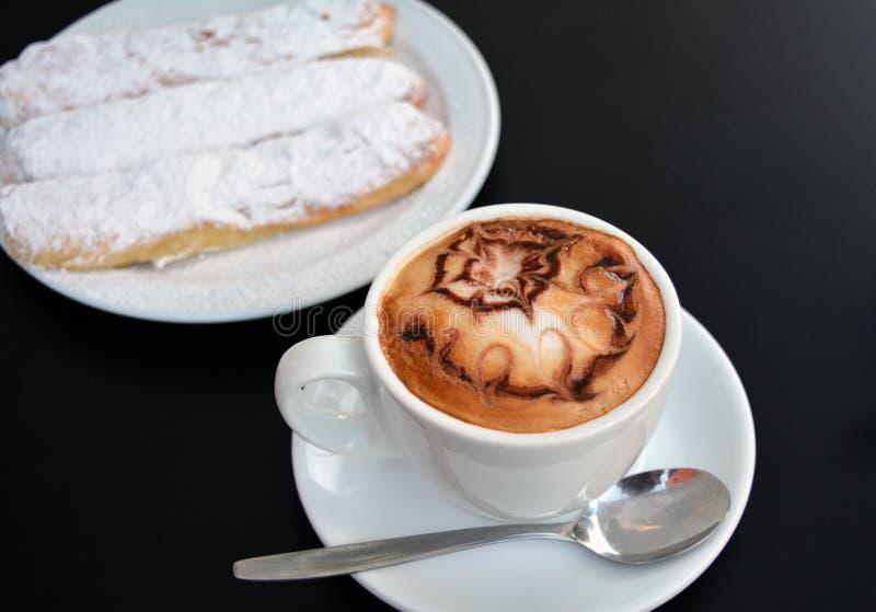 Copo do cappuccino e da sobremesa espumosos em uma tabela preta fotos de stock royalty free