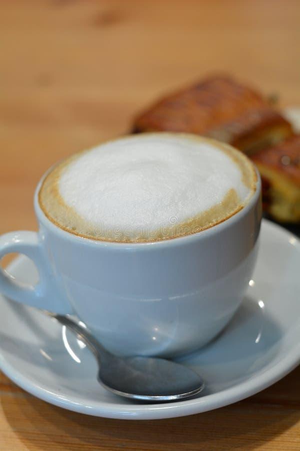 Copo do cappuccino e da sobremesa quentes na tabela de madeira fotografia de stock