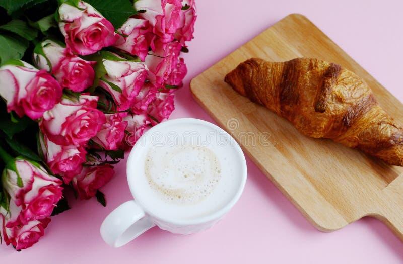 Copo do cappuccino e do croissant saboroso com rosas cor-de-rosa imagem de stock royalty free