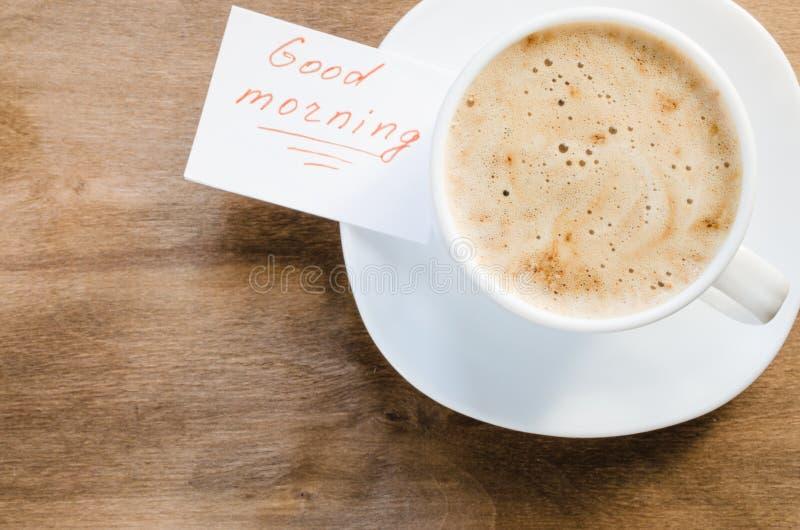 Copo do cappuccino e o bom dia da inscrição fotografia de stock