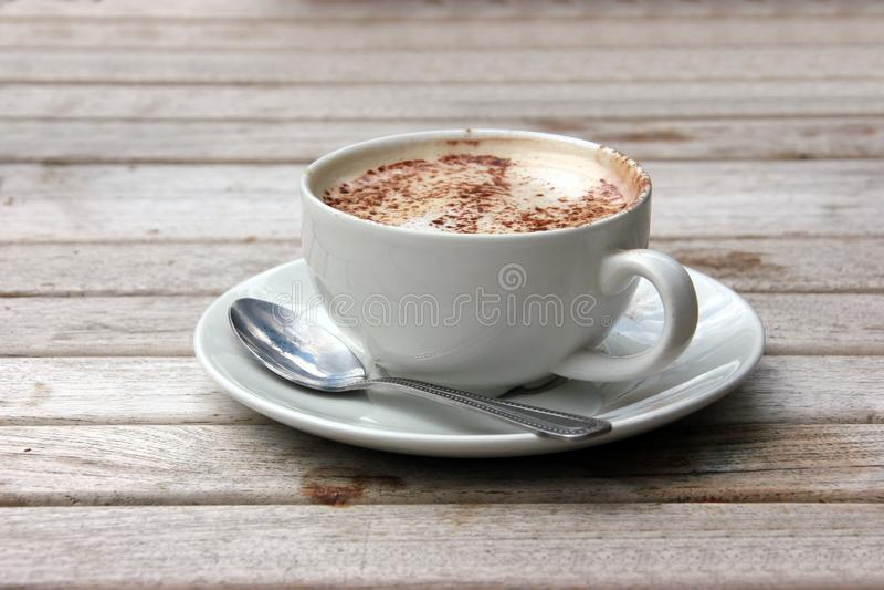 Copo do Cappuccino na tabela de madeira do slat fotografia de stock