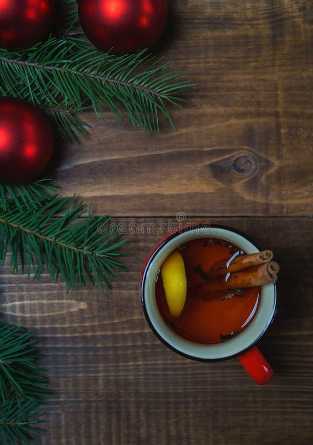 Copo do chá aromático quente com varas e limão de canela com ramos de árvore do Natal e de bolas vermelhas no fundo de madeira da imagem de stock royalty free