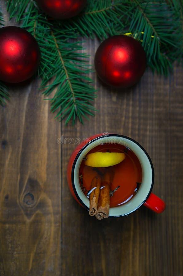 Copo do chá aromático quente com varas e limão de canela com ramos de árvore do Natal e de bolas vermelhas no fundo de madeira da imagem de stock