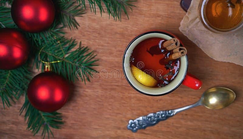 Copo do chá aromático quente com varas e limão de canela com ramos de árvore do Natal e de bolas vermelhas no fundo de madeira da fotografia de stock