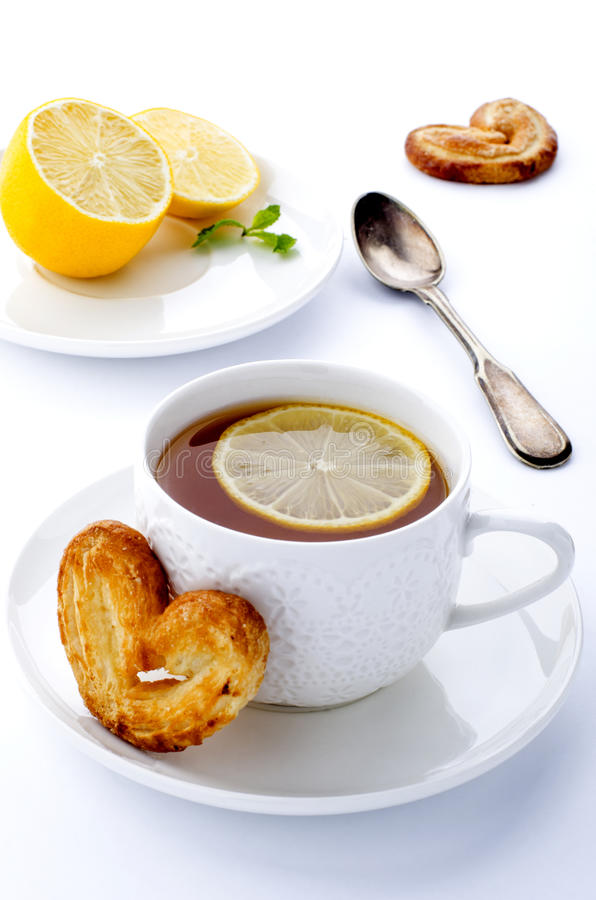 Copo do chá com limão e pretzeis imagens de stock