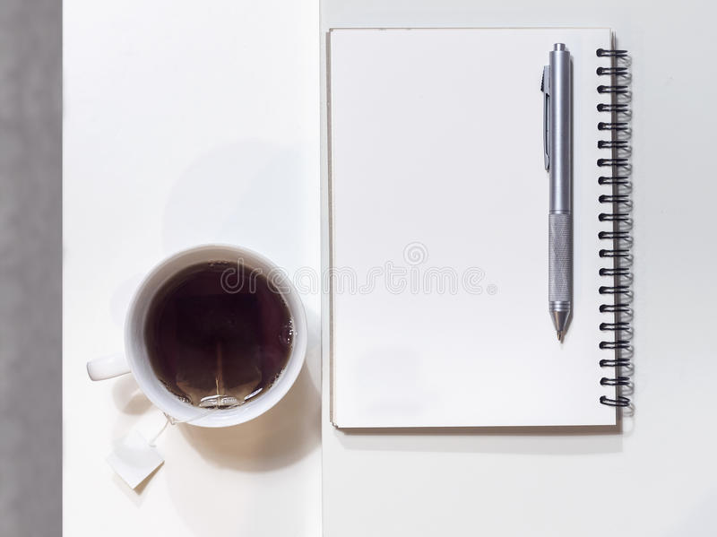Copo do chá com livro e da pena na tabela imagens de stock royalty free