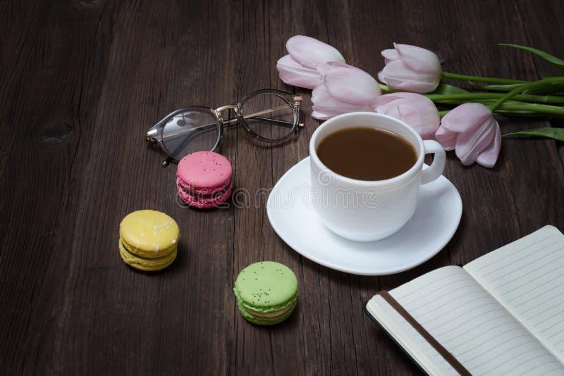Copo do chá, dos macarons, dos vidros, de tulipas cor-de-rosa e de caderno no woode imagem de stock