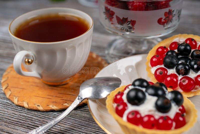 Copo do chá e das cestas com creme e corinto imagem de stock