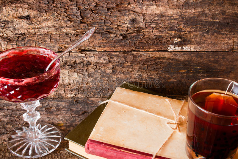 Copo do chá em uma pilha de livros ao lado de uma corda amarrada para bloquear em um vaso fotografia de stock royalty free