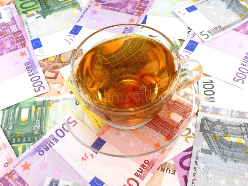 Copo do chá ou de café no papel de parede do dinheiro foto de stock royalty free