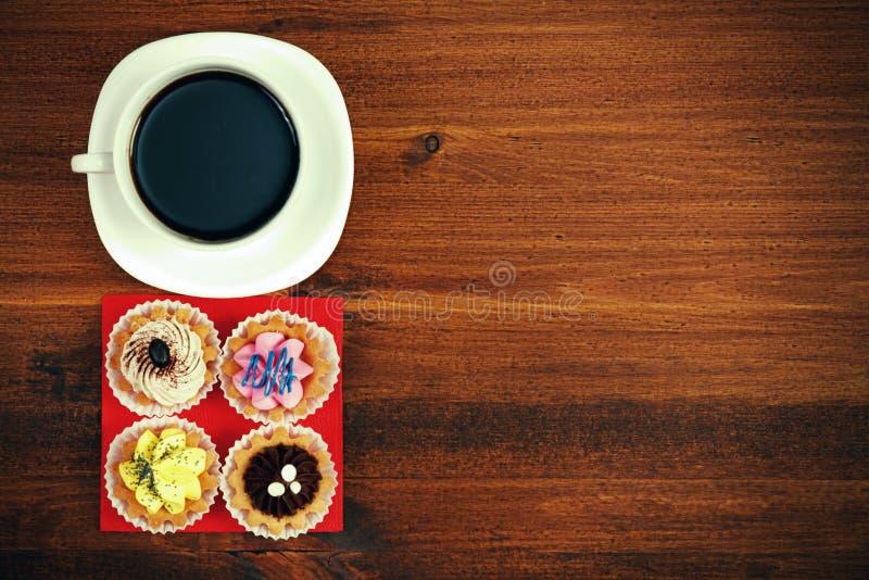 Copo do chá ou o café e os quatro queques na tabela marrom imagens de stock royalty free