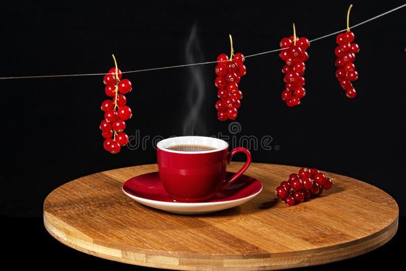 Copo do chá quente em uma tabela de madeira cercada por bagas do corinto vermelho em um fundo preto imagens de stock royalty free