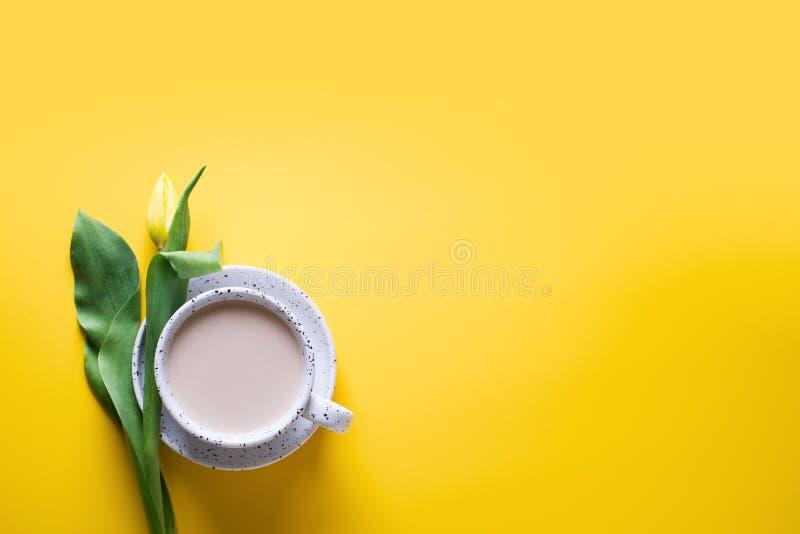 Copo do coffe com tulipas amarelas sobre o fundo amarelo imagem de stock royalty free