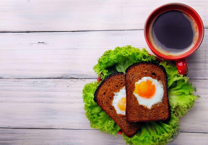 Copo do coffe e dois ovos fritos no brinde na salada Vista superior imagens de stock
