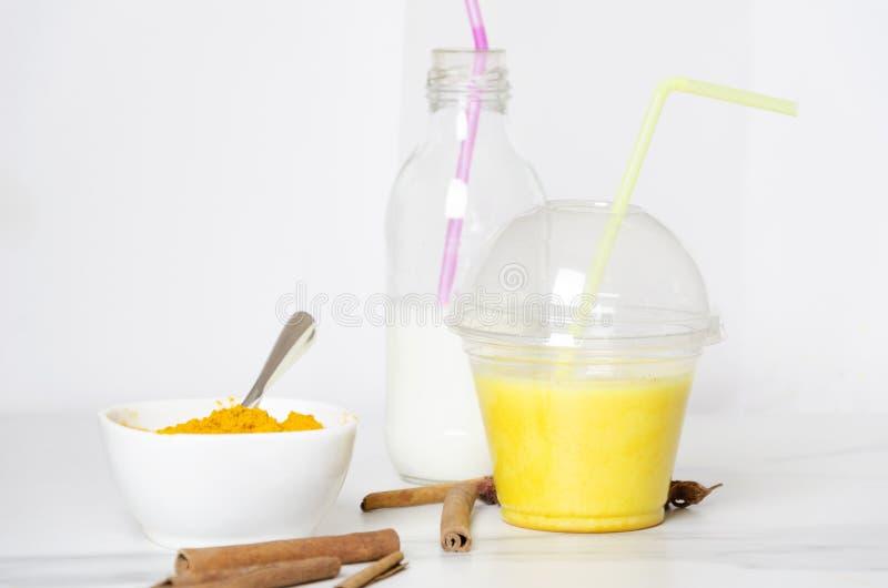 Copo do leite dourado, garrafa do leite, cúrcuma, canela Latte fortasty da cúrcuma dos ingredientes imagem de stock