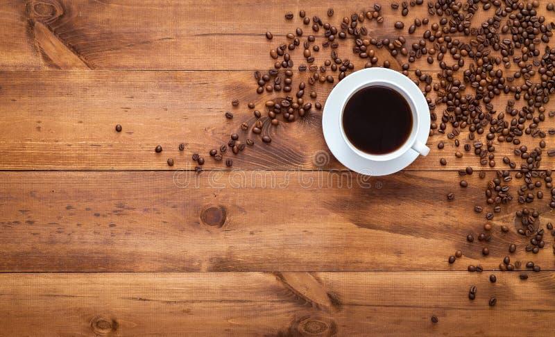 Copo dos feijões pretos do café e do cofee da manhã dispersados na tabela de madeira marrom, fundo escuro da loja do café do arom fotografia de stock royalty free