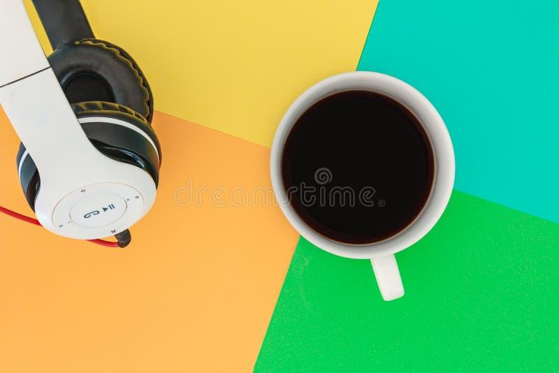 Copo a dos fones de ouvido e de café na placa brilhante colorida da diferença Conceito da m?sica fotografia de stock royalty free