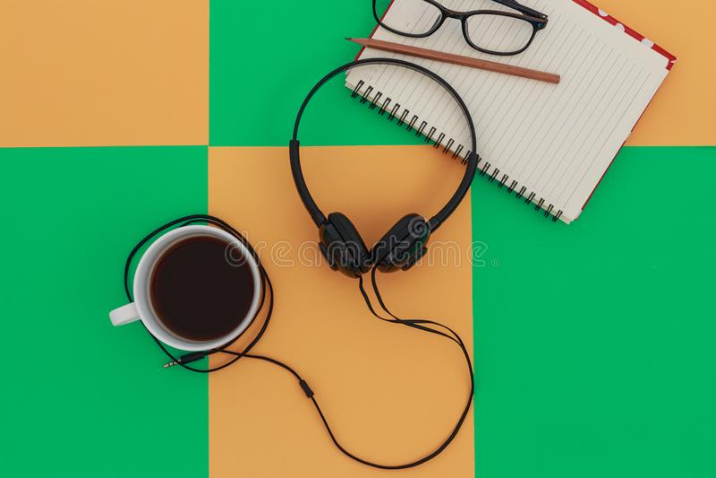 Copo a dos fones de ouvido e de café na placa brilhante colorida da diferença Conceito da m?sica fotografia de stock