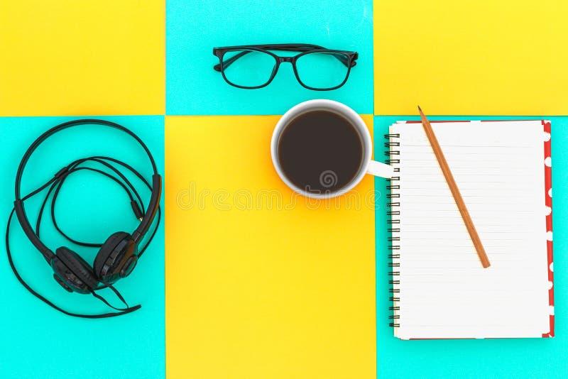 Copo a dos fones de ouvido e de café na placa brilhante colorida da diferença Conceito da m?sica Vista superior foto de stock royalty free