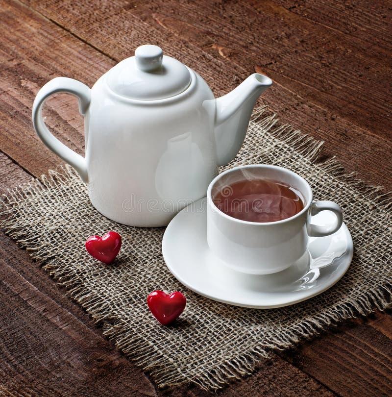 Copo e bule de chá com corações vermelhos imagem de stock