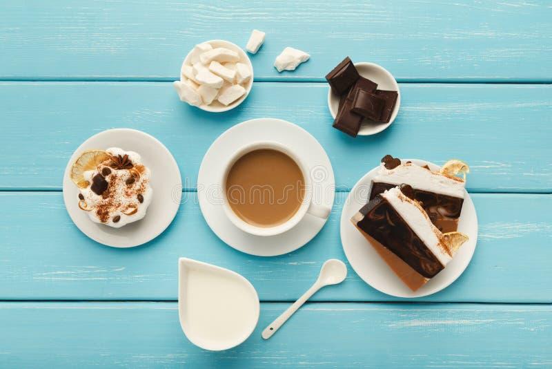 Copo e doces de café na tabela de madeira do vintage azul, vista superior fotos de stock