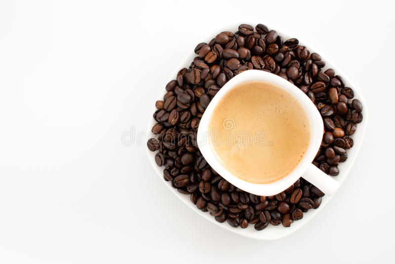 Copo e feijões de café em um fundo branco imagens de stock