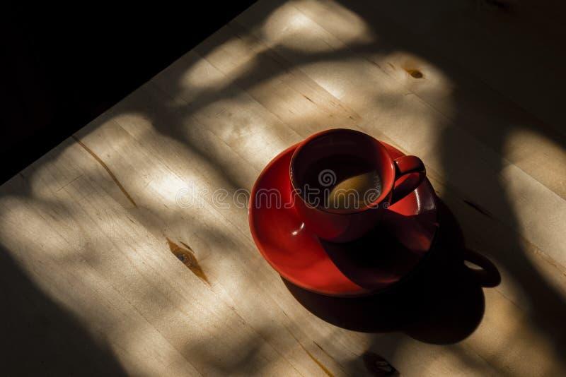 Copo e pires vermelhos na tabela de madeira com sombras imagens de stock royalty free