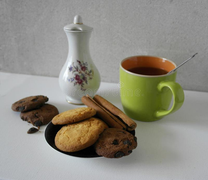 Copo e potenciômetro do café e dos feijões de café, cookies com canela, doces de chocolate, isolados no branco foto de stock royalty free