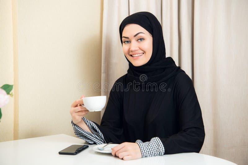 Copo guardando muçulmano fêmea novo atrativo da caneca de café que senta-se em casa e que sorri à câmera imagens de stock royalty free