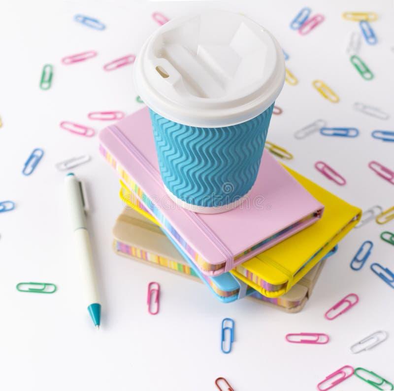 Copo, pena e blocos de notas de café de papel azul isolados no fundo branco fotos de stock