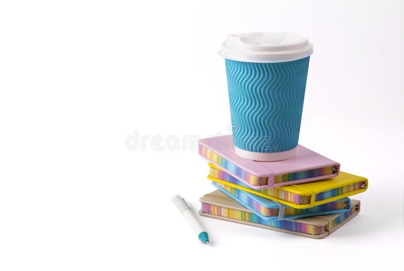 Copo, pena e blocos de notas de caf? de papel azul isolados no fundo branco imagem de stock royalty free