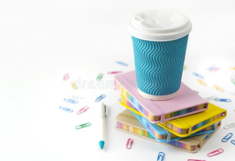 Copo, pena e blocos de notas de caf? de papel azul isolados no fundo branco foto de stock royalty free