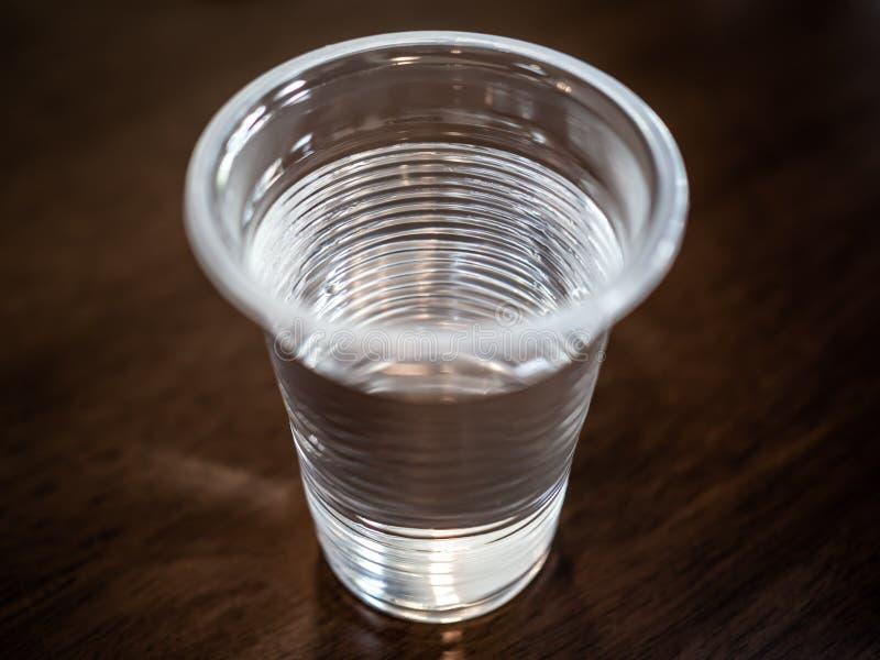 Copo plástico de Transparnt com água na tabela de madeira fotografia de stock
