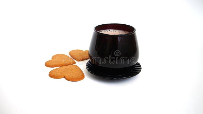 Copo preto com as cookies quentes da bebida e da aveia sob a forma do coração foto de stock