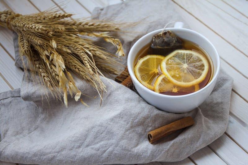 Copo quente do chá com limões, canela e trigo imagens de stock