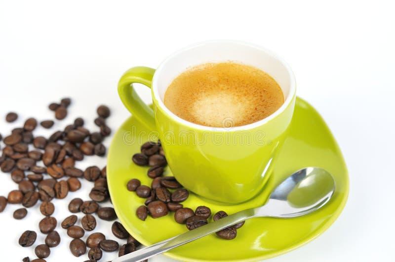 Copo verde do café com feijões e colher de café fotografia de stock