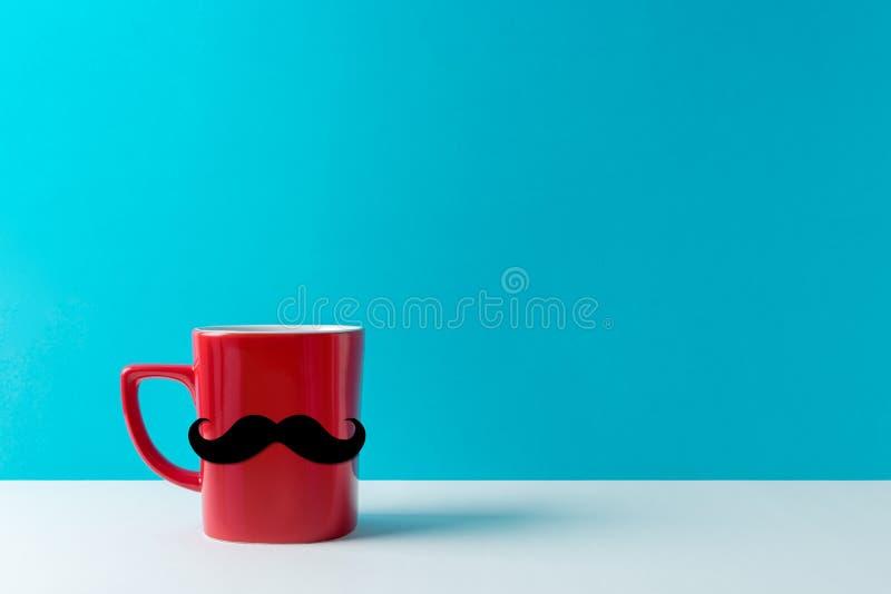 Copo vermelho com o bigode na tabela branca sobre o fundo azul foto de stock royalty free