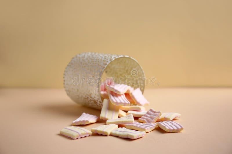 Copo virado com os marshmallows doces na tabela de cor imagens de stock
