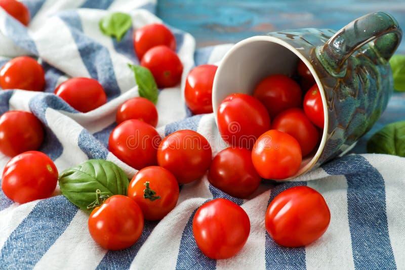 Copo virado com os tomates de cereja frescos na tabela imagem de stock royalty free