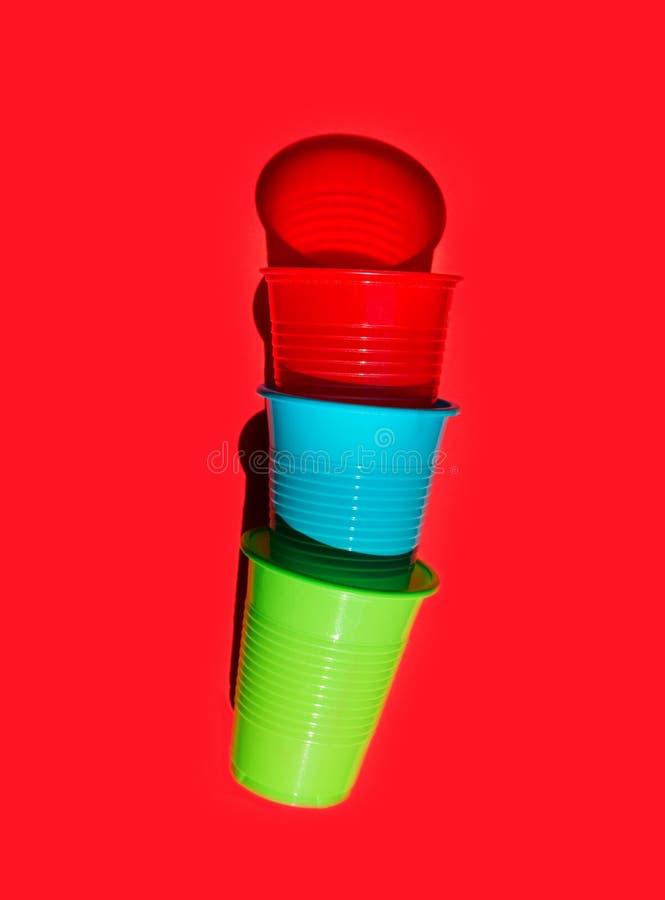 Copos bebendo plásticos coloridos empilhados no fundo vermelho contínuo Alternativas plástico-livres da proteção ambiental imagem de stock royalty free