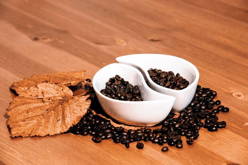 Copos com feijões de café em uma tabela de madeira foto de stock