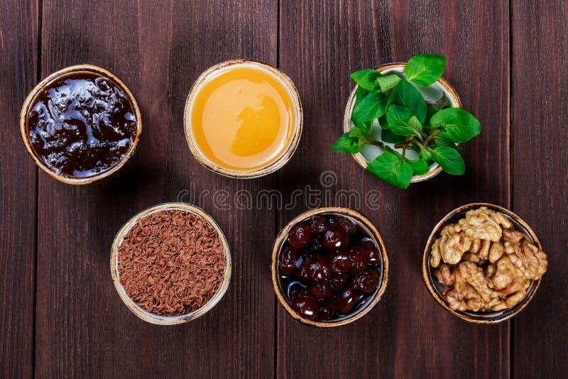 Copos da parcela de ingredientes saudáveis na tabela de madeira escura, doce, mel, hortelã, chocolate raspado, doce de cereja, no imagem de stock royalty free