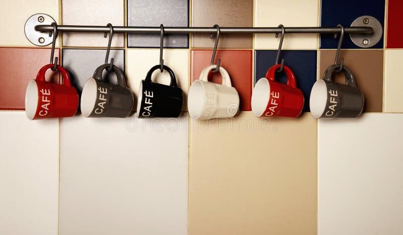 Copos de café coloridos nos ganchos foto de stock