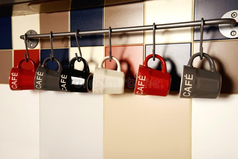 Copos de café coloridos nos ganchos fotos de stock royalty free