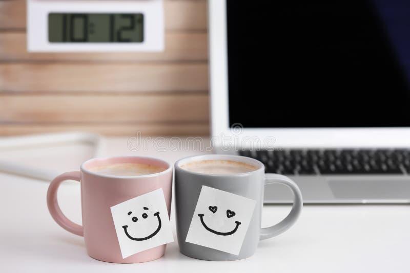 Copos de café com etiquetas bonitos na tabela foto de stock