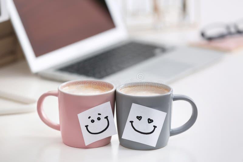 Copos de café com etiquetas bonitos na tabela imagens de stock